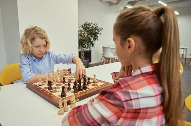 Ernster kleiner kaukasischer junge, der seinen zug macht, während er schach mit einem freund spielt, der zusammen sitzt?