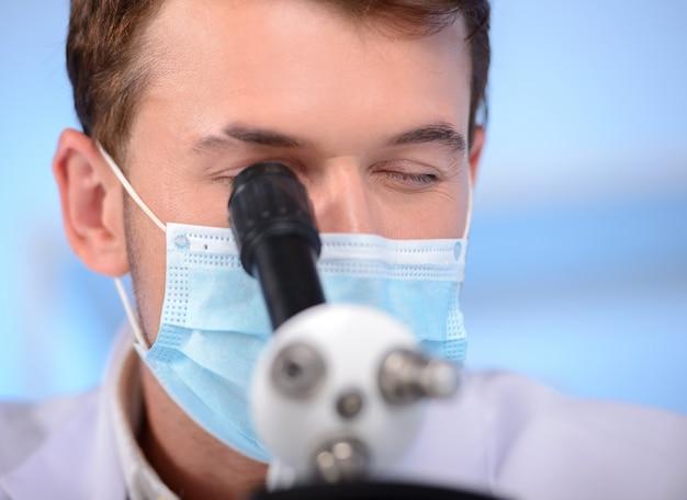 Ernster kliniker, der chemisches element im labor studiert.