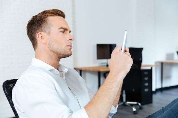Ernster konzentrierter junger geschäftsmann, der bei der arbeit tablette sitzt und benutzt