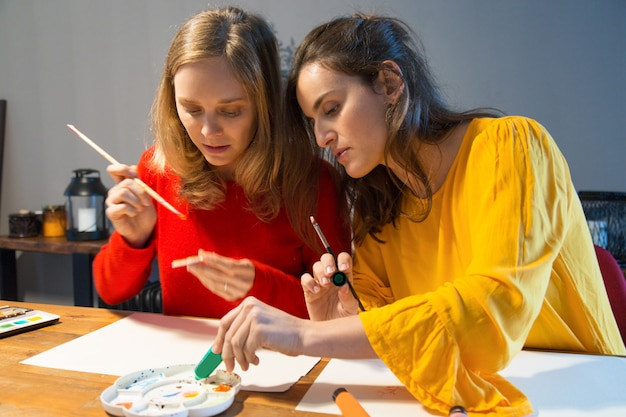 Ernster kunstmeister, der zeigt, wie man mit palette arbeitet