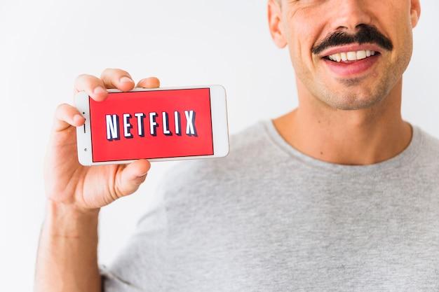 Ernster lächelnder kerl, der netflix-logo auf smartphone zeigt