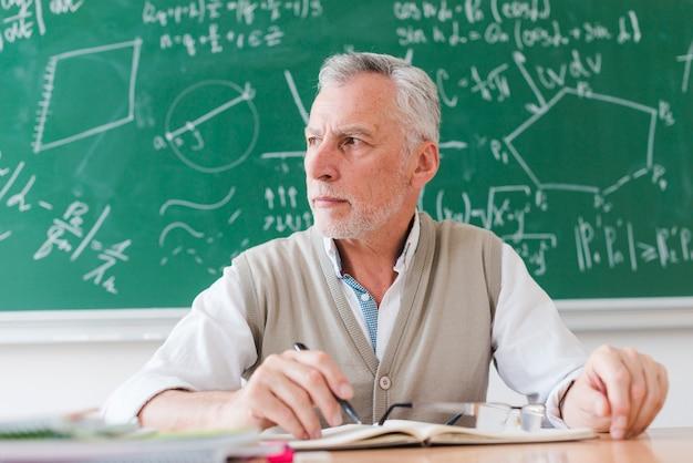 Ernster lehrer, der weg im klassenzimmer schaut