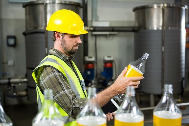 Ernster männlicher arbeiter, der flaschen in der saftfabrik inspiziert