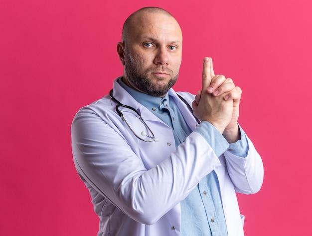 Ernster männlicher arzt mittleren alters, der ein medizinisches gewand und ein stethoskop trägt und nach vorne schaut, die pistolengeste isoliert auf rosa wand?