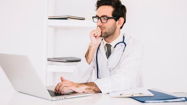 Ernster männlicher doktor, der an laptop in der klinik arbeitet