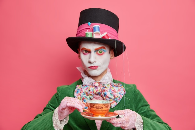 Ernster männlicher hutmacher aus dem wunderland trinkt tee auf party sieht streng in der kamera aus trägt spezielles kostüm bereit für halloween-karneval isoliert über rosa wand