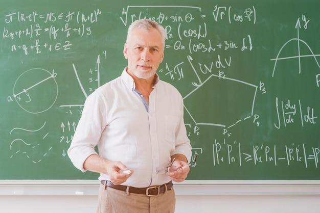 Ernster männlicher lehrer, der an der tafel mit diagramm und gleichung steht und kamera betrachtet