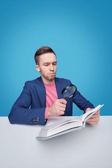Ernster männlicher leser mit lupe, die durch schreibtisch sitzt und durch text auf seite des buches schaut