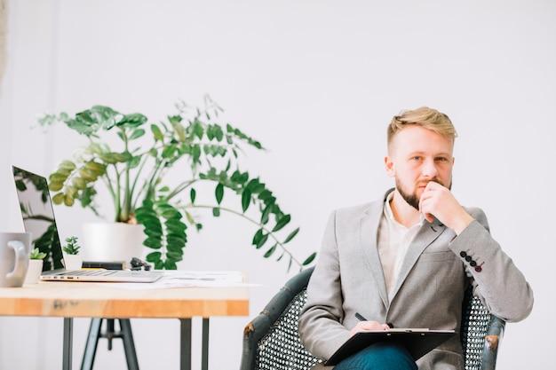 Ernster männlicher psychologe, der mit klemmbrett und stift auf stuhl sitzt