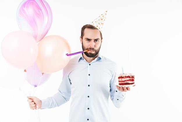 Ernster mann bläst partyhorn und hält geburtstagskuchen mit luftballons isoliert über weißer wand