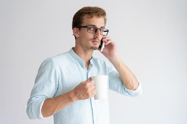Ernster mann, der becher hält und auf smartphone spricht