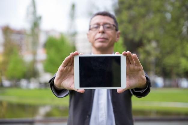 Ernster mann, der dem zuschauer tablettenschirm im park zeigt