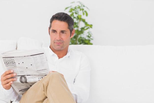 Ernster mann, der ein nachrichtenpapier im wohnzimmer liest