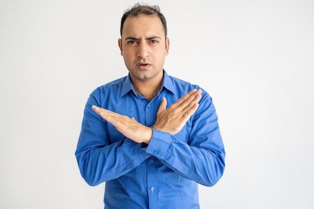 Ernster mann, der gekreuzte hände zeigt und kamera betrachtet