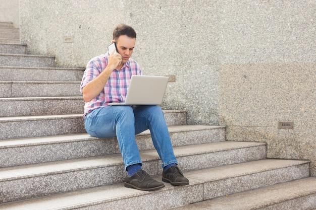 Ernster mann, der handy verwendet und datei auf laptop überprüft