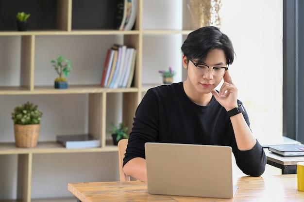 Ernster mann, der im kreativbüro sitzt und mit laptop-computer arbeitet.