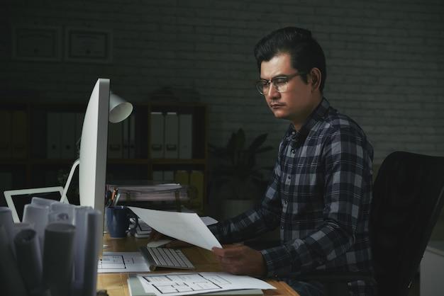 Ernster mann, der mit dokumenten in seinem büro arbeitet
