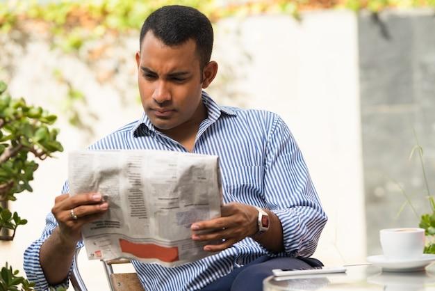 Ernster mann, der zeitung im im freiencafé liest