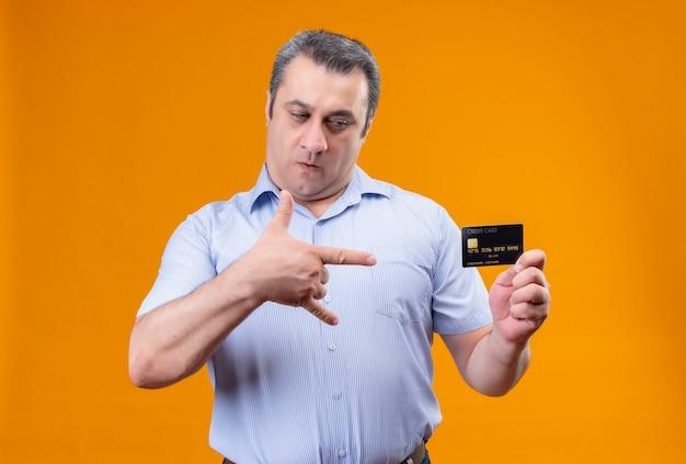 Ernster mann des mittleren alters im blau gestreiften hemd, das kreditkarte auf einem orange hintergrund betrachtet
