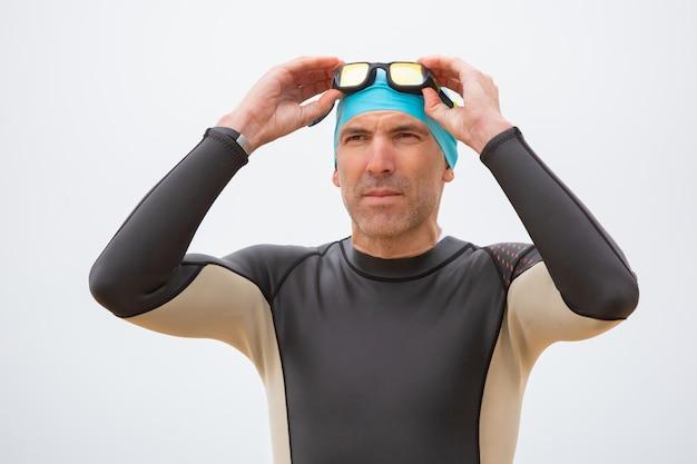 Ernster mann im neoprenanzug mit schutzbrille