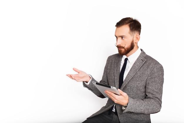 Ernster mann in der grauen klage spricht etwas, das tablette in seinem arm hält