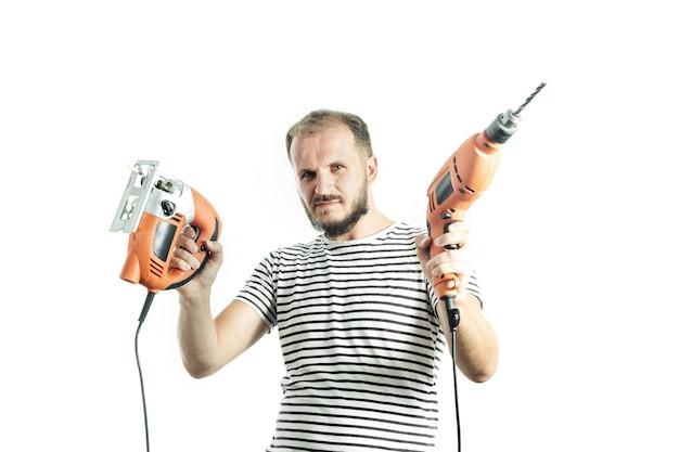 Ernster mann in einem gestreiften t-shirt hält einen bohrer und eine elektrische stichsäge in den händen isoliert auf weiß
