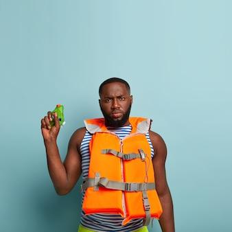 Ernster mann mit dunkler haut, dicken borsten, hält kleine wasserpistole, kümmert sich um sicherheit