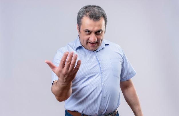 Ernster mann mittleren alters im blau gestreiften hemd, das näher mit handgeste auf weißem hintergrund anruft