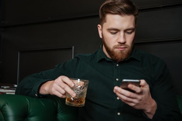 Ernster mann sitzt in einem sessel und trinkt whisky mit handy und schaut darauf.