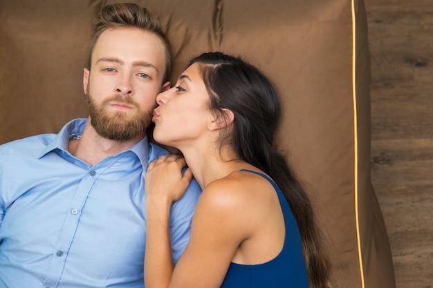 Ernster mann und frau glücklich ihn auf der couch küssen