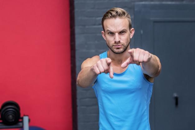 Ernster muskulöser mann, der seine finger zeigt
