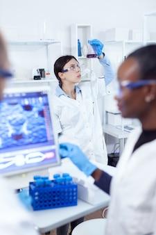 Ernster nachdenklicher wissenschaftler, der farbe auf flüssigkeit in glaskolben analysiert. multiethnisches team medizinischer forscher, die im sterilen labor mit schutzbrille und handschuhen zusammenarbeiten.