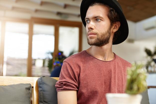 Ernster oder trauriger attraktiver junger bärtiger student, der trendigen schwarzen hut trägt, der allein im modernen geräumigen café sitzt