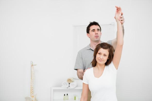 Ernster osteopath, der den arm eines patienten anhebt