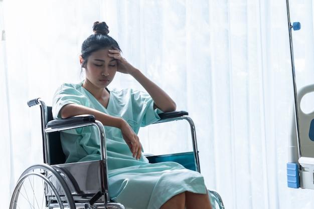 Ernster patient, der auf rollstuhl im krankenhaus sitzt.