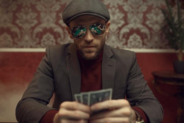 Ernster pokerspieler mit sonnenbrille, der im casino spielt. sucht