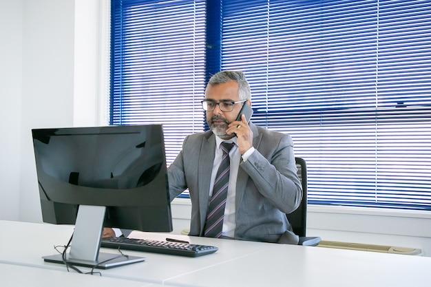 Ernster reifer geschäftsleiter, der auf handy spricht, während er computer am arbeitsplatz im büro benutzt. mittlerer schuss. digitales kommunikations- und multitasking-konzept