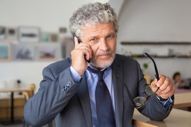 Ernster reifer geschäftsmann, der auf handy spricht, bei der zusammenarbeit steht, sich auf schreibtisch stützt, kamera betrachtet, brille hält