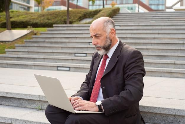 Ernster reifer geschäftsmann unter verwendung des laptops in der straße