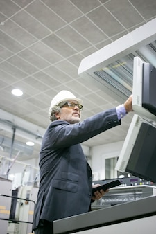 Ernster reifer männlicher anlageningenieur, der industriemaschine betreibt, knöpfe auf dem bedienfeld drückt und tablette hält