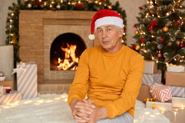 Ernster reifer mann, der auf boden auf weißem teppich nahe geschmücktem tannenbaum sitzt