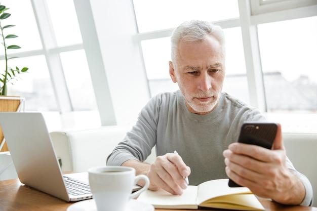 Ernster reifer mann, der sich notizen macht, während er mit laptop und handy im café drinnen arbeitet?