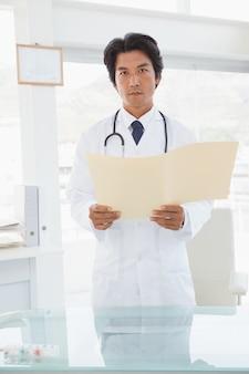 Ernster schauender doktor mit medizinischen dateien