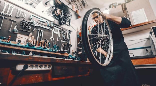 Ernster schöner kaukasischer mann, der fahrradrad in den händen hält, während in werkstatt steht.