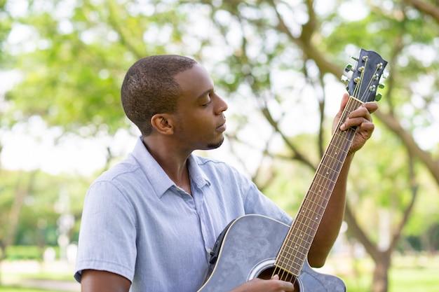 Ernster schwarzer mann, der gitarre im park spielt