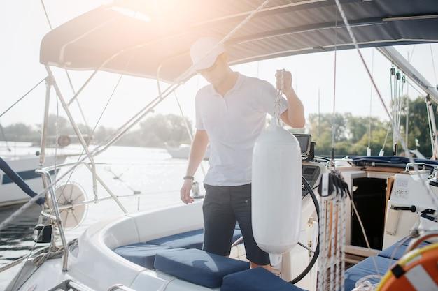 Ernster seemann steht auf seiner yacht und schaut nach unten. er hält seil mit großer plastikflasche. der junge mann ist ruhig und friedlich. die sonne geht unter