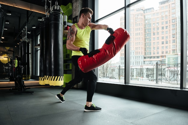 Ernster sportler, der übungen mit boxsack im fitnessstudio macht