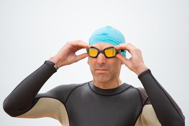 Ernster sportler im neoprenanzug mit schutzbrille