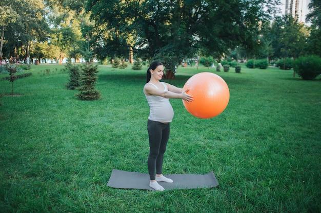Ernster stand der jungen schwangeren frau auf yogakamerad outisde im park. sie trainieren mit großen orange fitness-ball. model halte es vor sich.