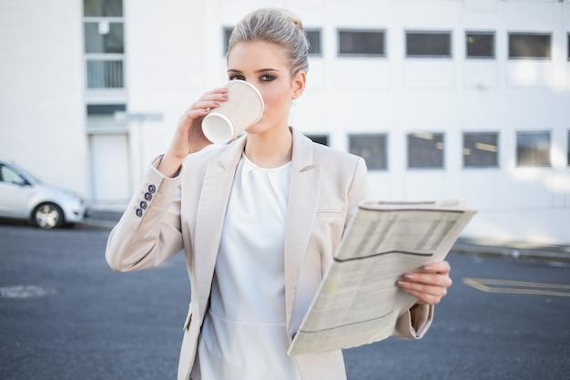 Ernster stilvoller geschäftsfrautrinkender kaffee